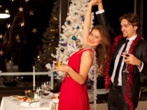 Happy young couple with champagne glasses dancing at christmas